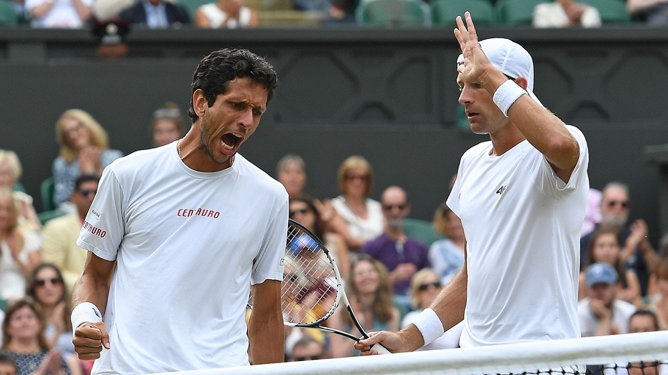 Poland's Lukasz Kubot (R) and Brazil's Marcelo Melo react after winning a point against Austria's Oliver Marach and Croatia's Mate Pavic during their men's doubles final match on the twelfth day of the 2017 Wimbledon Championships at The All England Lawn Tennis Club in Wimbledon, southwest London, on July 15, 2017. / AFP PHOTO / Glyn KIRK / RESTRICTED TO EDITORIAL USE        (Photo credit should read GLYN KIRK/AFP/Getty Images)